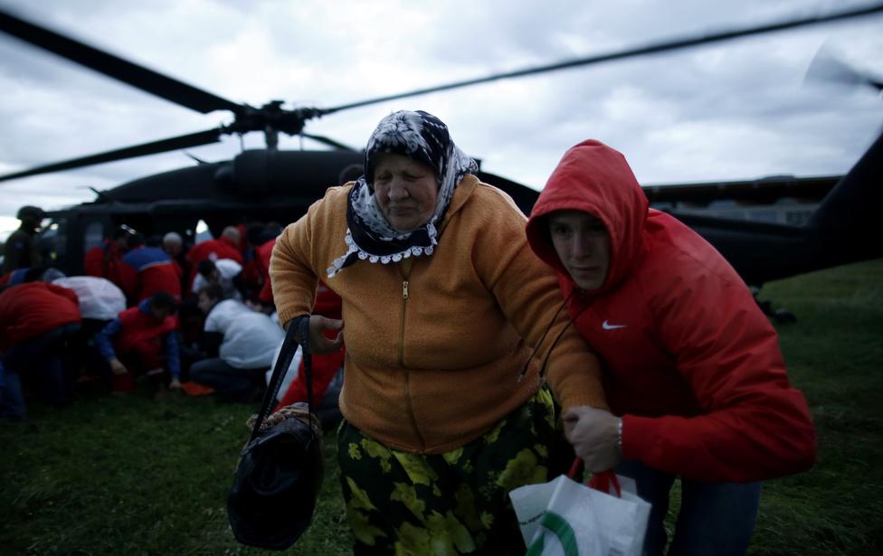 Anya és fia távolodnak egy EUFOR helikoptertől, ami kimenekítette őket az áradás miatt veszélyessé vált Serici faluból. A helikopter a közép-boszniai Zenicában szállt le az emberekkel. Szerbiában és Boszniában több mint harmincan haltak meg az áradások következtében, és ezrek voltak kénytelenek elhagyni otthonukat.