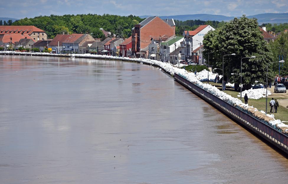 Emberek sétálnak a Sava folyó mentén, homokzsákokból épített gátak védelmében Sremska Miltrovicában, Belgrádtól 70 kilométerre nyugatra.