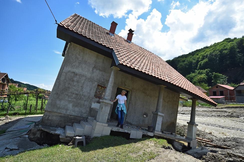 Pavlovic Oksana áll a földcsuszamlásban lakhatatlanná vált háza tornácán Krupanjnál,  130 kilométerre dél-nyugatra a szerb fővárostól, Belgrádtól. A települést az áradás 4 napig elzárta a külvilágtól. A szinte az egész Balkánt érintő katasztrófa alatt sok helyen kizárólag csónakokkal és helikopterekkel folyt a mentés, az áradó folyók miatt ugyanis szárazföldi úton megközelíthetetlenek a települések.