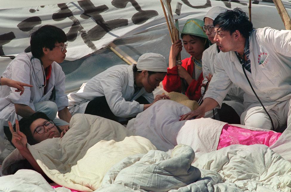 A Tienanmen, azaz Mennyei béke tér a Ming-dinasztia alatt 1415-ben épült Mennyei béke kapujáról kapta, mely a Tiltott Várostól elválasztja. A teret Mao Ce-tung az ötvenes évek végén kibővíttette, területe 440 ezer négyzetméter lett, ezzel Mao elképzeléseinek megfelelően a világ legnagyobb tere lett. Mao egyébként itt kiáltotta ki a népköztársaságot 1949-ben, és itt áll mauzóleuma is – bebalzsamozott testét ugyanúgy meg lehet nézni, mint Leninét a Vörös téren, bár mindkettőről sokan azt gyanítják, valójában viaszbábuval helyettesítették az eredeti testet. A képen mentősök ápolják a legyengült tüntetőket május végén.