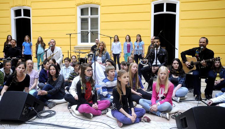 Résztvevők éneklik a Nemzeti összetartozás dalát a budapesti Hadtörténeti Intézet udvarán 2013. június 4-én a nemzeti összetartozás napján. A diákok mögött ül a dal két szerzője Bársony Bálint (b5 fehér zakóban) és Gergely Éva (k) valamint Kállay-Saunders András énekes (j2).