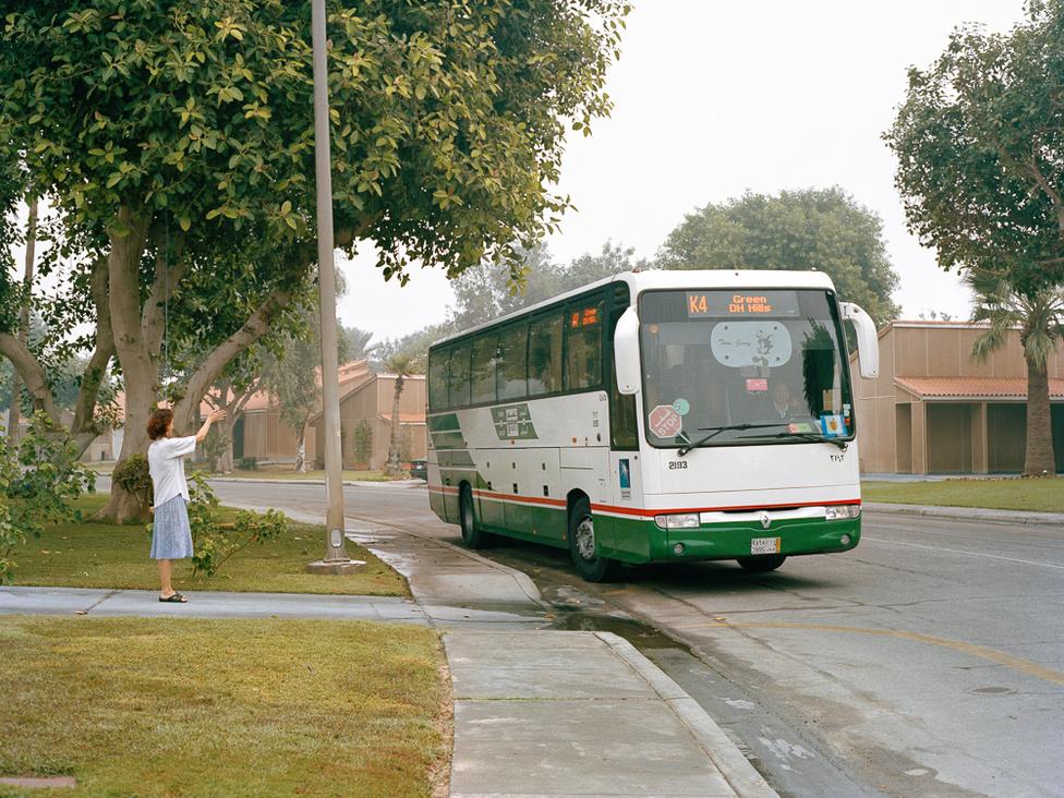 Anya integet a busszal iskolába induló kislányának. Hagyományos, sárga, amerikai iskolabuszokat is látni a városban, de ezekkel dolgozókat szállítanak egyik helyről a másikra.