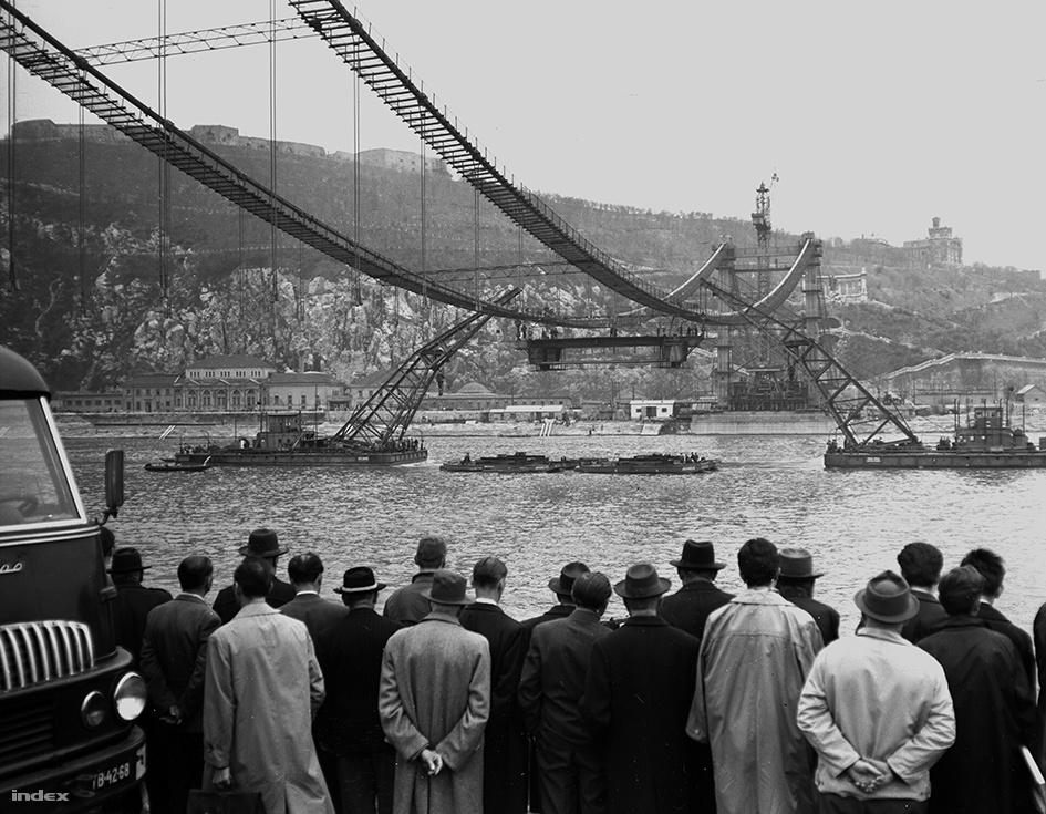 Az Erzsébet híd első járótagjának beemelése és rögzítése a káblekhez, a József Attila és Ady Endre nevű úszódaruk segítségével. A híd eredetijét a második világháború során, 1945 januárjában a visszavonuló német csapatok felrobbantották, helyére pedig kábelhíd épült, aminek építését tömegek figyelték a Duna mindkét partjáról. A szélben olykor balesetek is előfordultak, volt olyan MTI-s fotós, akinek a felszerelése bánta a kalandot.