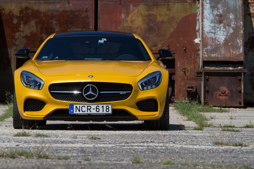 A Mercedes kitartóan próbál betörni a szupersportautók közé, ez már a harmadik próbálkozása. Az első, a McLaren SLR nem volt túl sikeres, a 3500 tervezettből csak nagy nehezen adtak el 1400-at 2003-2010 között, majd utódja - a sirályszárnyas SLS AMG - próbálkozott, de hiába volt sokkal sportautósabb elődjénél, alig 10 ezer eladott példány után belátták, hogy a 200+ ezer euróért a vásárlók maximum orrmotoros Ferrarit és szupersportautókat vagy überluxus-szedánokat hajlandóak szemmel látható tételben vásárolni. Ezért az AMG GT/GTS árát is nagyjából harmadával csökkentették és lehozták a hasonló teljesítményű Porsche 911-esek szintjére. Utóbbival előszeretettel hasonlítják össze mindenütt, hiszen mint menetteljesítményben úgy árban is nagyjából konkurensek, de ez öreg hiba, ez az autó ugyanis - mint a neve is mondja - egy GranTurismo. Ez az AMG Solarbeam (+ 2,3 millió felár) fényezésű GTS pedig annak a keményebb, sportosabb változata. Ha húszezresekkel tapétázták volna ki, olcsóbb lett volna, külön idegesítő, hogy nem sikerült egyformára fényezni a műanyag és fém elemeket.