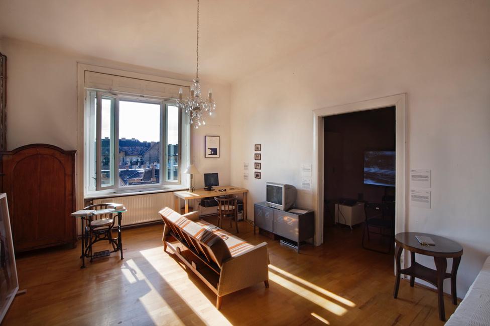 """A Népszínház utcai lakás nappalija a kiállítás epicentruma:  Az íróasztalra helyezett képernyőn látható videóban a tökéletes brit akcentus keserves elsajátításának folyamatába kaphatunk betekintést (Katarina Zdjelar munkája), Krsto Papic Különvonatok című 1972-es dokumentumfilmje pedig a Németországba induló jugoszláv """"vendégmunkások"""" tömeges kivándorlásának megrázó és megindító krónikája."""