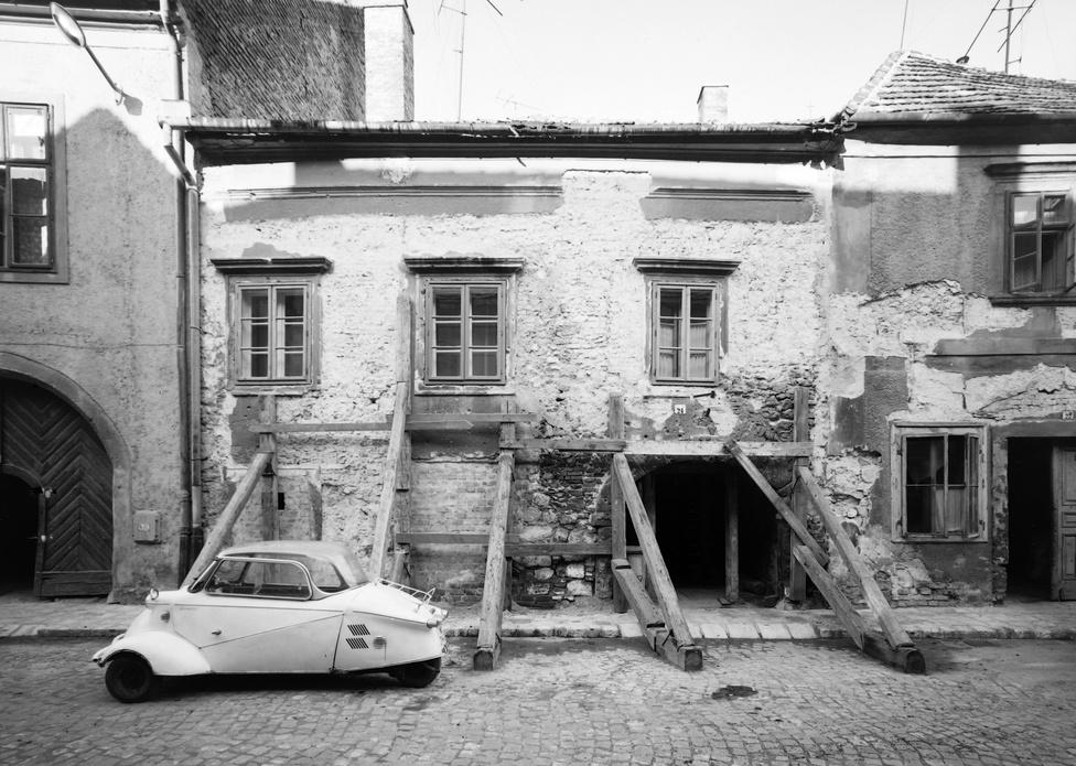 A helyszín ismét Sopron, néhány évvel később. A képen egy Messerschmitt Kabinenroller, amelyből                         nem sok közlekedett kis hazánkban, ám történelmileg másként is alakulhatott volna. Magyarországra az                          1950-es években begyűrűzött a törpeautó-láz: ezek motorkerékpár-motoros szerkezetek voltak, amelyben                          két személy tudott relatív kényelemben utazni. Urbach László, aki a második világháború előtt a Mátra                          motorkerékpárokat készítette, s akinek a Dongó segédmotoros kerékpárt és a Berva robogót is köszönhetjük                          az 1950-es években rávette a Kohó- és Gépipari Minisztériumot, hogy próbálják megvásárolni a                          Messerschmitt Kabinenroller liszenszét. Éppen akkor állították át a hadi termelésre fókuszáló vállalatokat                          civil termékekre, s így a budaörsi Prés- és Kovácsoltárugyárban zajlottak az előkészítő munkálatok,                          amelyeknek végül az 1956-os forradalom vetett véget