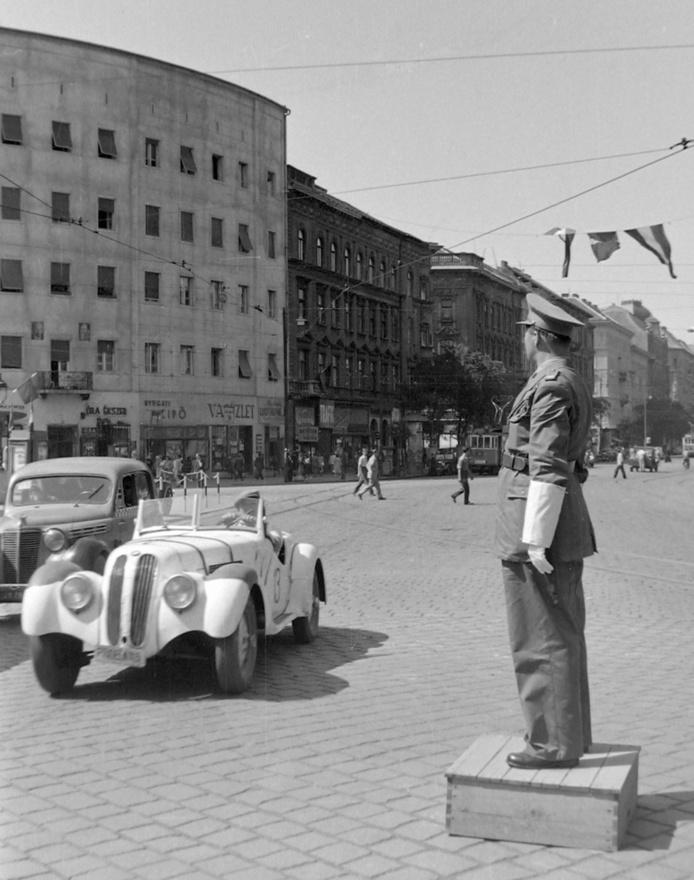 """Életkép az 1940-es évek végéről. Ami igazán különlegessé teszi ezt a képet az a fehér sportkocsi. A                         BMW 328 a harmincas évek végén vágyott álomautó volt, amelyből Magyarországra nagyon keveset                          exportáltak. A második világháború után ez a helyzet megváltozott. Több helyről is hallott, de levéltári                          forrásokkal – érthető módon – nem alátámasztott visszaemlékezések szerint 1946-1947 körül valamelyik                          Minisztérium (vélhetően a Belügyminisztérium) megbízásából a korszak híres motorversenyzői, Szabó                          """"Kuksi"""" László, Puhony Nándor és mások megbízást kaptak, hogy hozzák haza a második világháborúban                          elhurcolt járműveket. Ezek az urak civilben rendőrök, katonák – szóval hivatásos állományban voltak. Kaptak                          üres forgalmikat, rendszámokat. Persze fogalmuk se volt merre keressék a Vörös Hadsereg vagy éppen a                          németek által elvitt autókat. Amerre jártak, ott ha megtetszett egy autó, gyorsan ráraktak egy magyar                          rendszámot, s vitték. Így mondhatta magáról egy időben Szabó """"Kuksi"""", hogy ő a """"legnagyobb BMW                          importőr"""". A képen látható 328-t az oldalára pingált rajtszám alapján Körmendi László kereskedő,                          motorversenyző használta."""