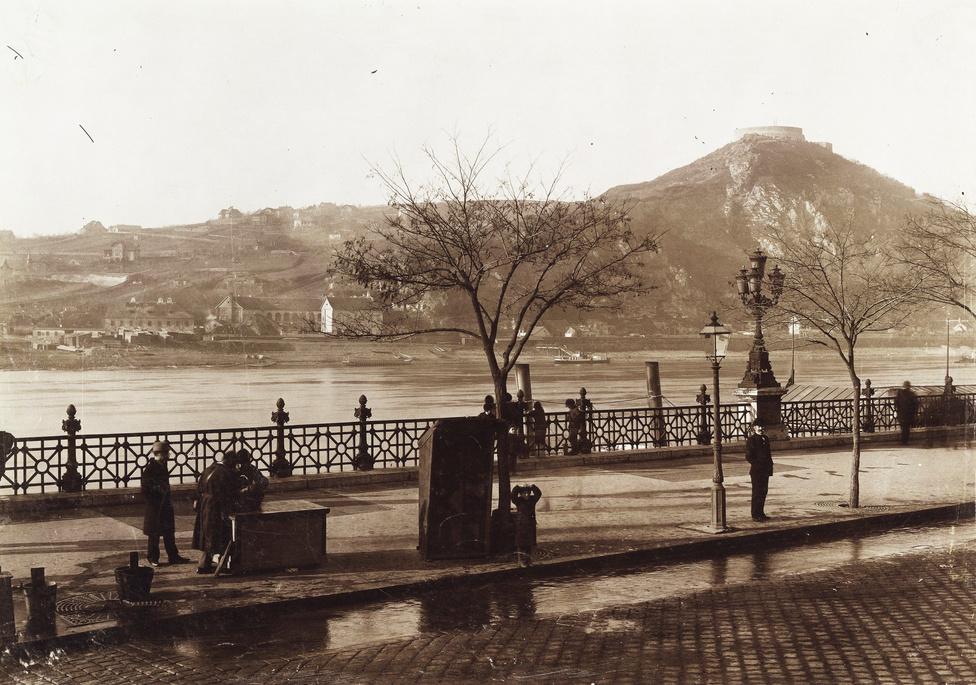 A rakpart a Fővám térnél. A Duna túlpartján a Sáros fürdő, az 1894-es bontás előtt, ami tényleg sáros volt: a nevét a víz alján leülepedett, gyógyhatású iszapról kapta. Ez volt a legrégebbi olyan fürdő Budapesten, amelyet nem a rómaiak alapítottak. Helyén építették a Gellért Szállót. Jobb oldalt a Gellért-hegy, tetején a Citadellával.