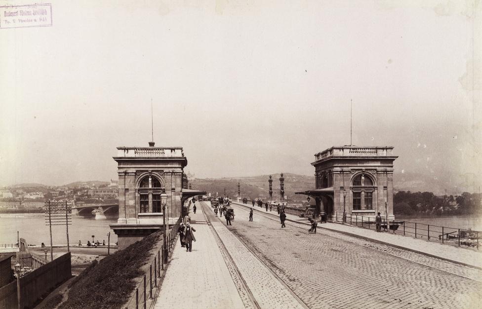 A Margit híd pesti hídfője a vámházakkal, 1896-ban. A túloldalt, a budai hídfő felett a Gül Baba türbéje köré épített Wagner villa is felsejlik.