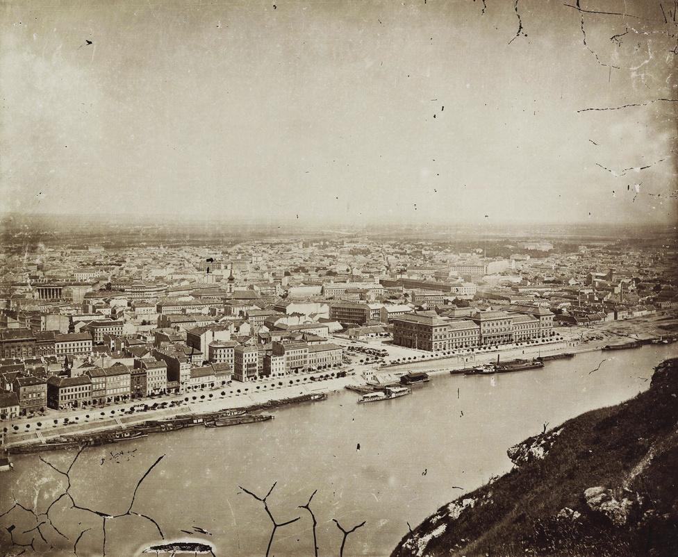 Pest látképe a Gellért-hegyről 1885-ben. Középpontban a Fővámház, amelyet Ybl Miklós tervezett – igaz terveit a városatyák kétszer is visszadobták, és végül a harmadik változat épülhetett meg. Az épület ma a Corvinus Egyetem központi épületeként ismert.