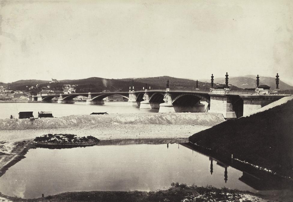 Pesti rakpart a Margit hídnál, ami Budapest második állandó hídja volt.  Tervpályázatát egy francia mérnök, Ernest Goüin nyerte meg, aki egyike annak a 72 tudósnak, akiknek a neve szerepel az Eiffel-torony oldalán is. A távolban a Rózsadomb látható.