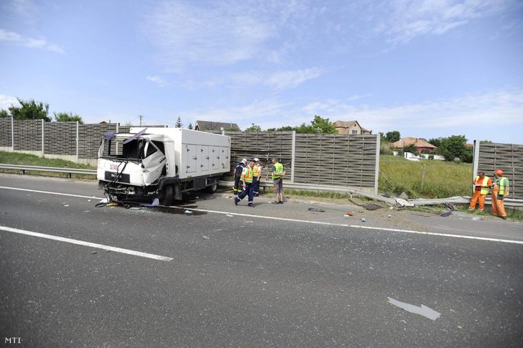 Rendőrök és tűzoltók dolgoznak egy összetört kisteherautó mellett 2015. június 4-én az M7-es autópálya fővárosból kifelé vezető oldalán a 18-as kilométernél ahol eddig tisztázatlan körülmények között a jármű elsodort négy férfit.