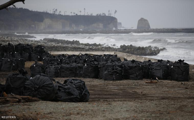 Sugárszennyezett talajfölddel teli zsákok állnak a tenger partján Tomioka mellett. A japán kormány tervei szerint a környéket 30 év alatt fogják tudni helyreállítani.