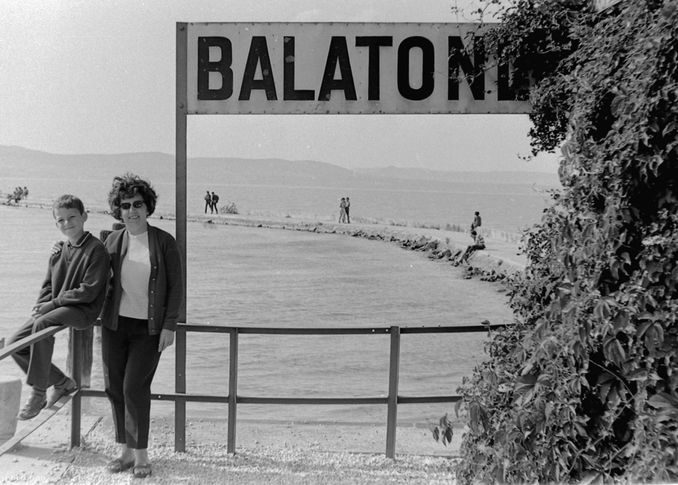 """A déli part egyik legnépszerűbb üdülőhelye a mai napig Balatonlelle. Bár sokan valószínűleg inkább Boglárlelleként ismerik, mivel 1978-ban ezen a néven egyesült Balatonboglárral (hogy aztán a rendszerváltás után végül mégis különváljanak). Lelle a politikai széljárástól függetlenül 100 éve közkedvelt nyaralóhely: már a Tanácsköztársaság is ide vitte le vonattal """"a kis proletárokat"""" a gyereknyaraltatási programja idején, a két világháború között Mussolini ifjúavantgardistáifürödtek itt, '36-ban pedig a Horthy-korszak ipari tanoncait is Lellére küldte kikapcsolódni az Országos Társadalombiztosítási Intézet. A szocializmusban pedig sok szálloda nyílt, és számos állami vállalat épített üdülőt a városban a Szakszervezetek Országos Tanácsától kezdve a TERTA telefongyárig A fenti kép 1968-ban készült, a lellei hajóállomás mólóján."""