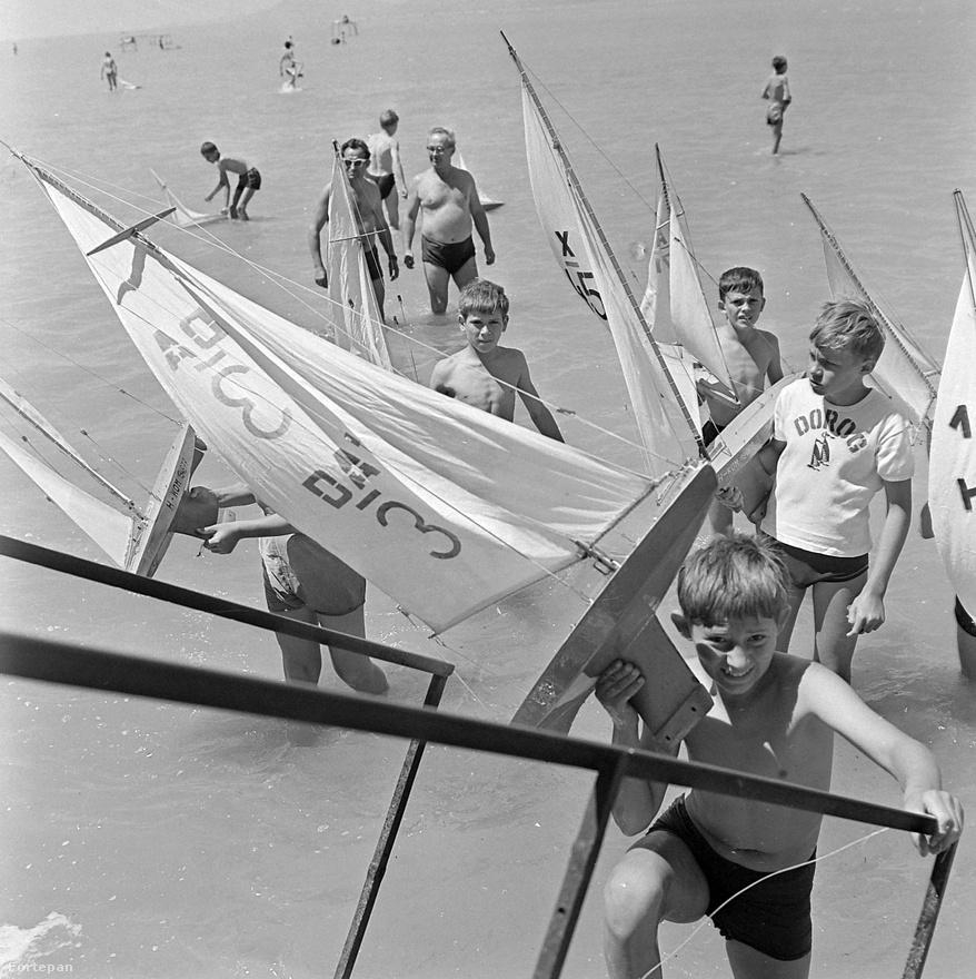 Balatonszemes a déli part kirakattelepülése volt a szocializmusban, akárcsak az északi parton Zánka. Az itteni egykori főúri nyaraló helyén, a Hunyady-telepen épült fel a mára már teljesen elfeledett gyermektábor, ahová a Szovjetunió úttörői jártak le nyaranta, hogy a magyar pajtásokkal közösen csobbanjanak a Balatonba. A fenti képen az 1968-as Hajómodellező Országos Úttörő Bajnokságon feszítenek kis lurkók, a délutáni technika szakkörök alatt barkácsolt vitorlásaikkal. Balatonszemes környéke egyébként nem csak a régi rendszer gyermekei között volt népszerű, hanem a felnőttek körében is: a szovjet úttörőtábortól nem messze, Balatonőszödön épült fel a Minisztertanács őrzött üdülője. Igen, ebből lett később az a kormányüdülő, ahol Gyurcsány Ferenc 2006-ban elmondta a híres beszédét.