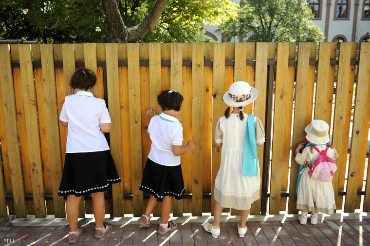 Gyerekek néznek ki a kerítésen a Szent Anna Katolikus Óvoda új épületének udvarán