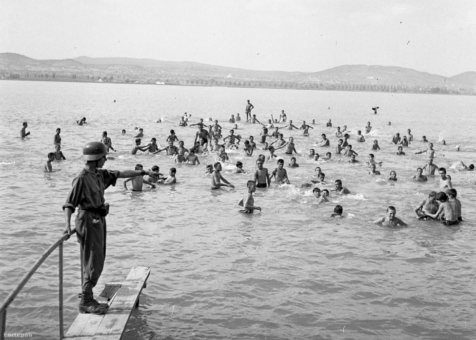 Sokan azt hiszik, a balatoni tömegnyaraltatást, és az ezzel járó hangos gyerekcsapatokat a kommunista úttörőmozgalom szabadította rá a csöndes balatoni üdülőövezetekre - de ez egyáltalán nem igaz. Már a Tanácsköztársaság idején is volt gyereknyaraltatási program, a két világháború közöttMussolini ifjúavantgardistáiis a magyar tengerben fürödtek, 1936-ban szintén a Balaton-partra küldte kikapcsolódni a Horthy-korszak ipari tanulóitaz Országos Társadalombiztosítási Intézet, és a fenti kép tanúsága szerint 1943-ban is a Tihany mellettiGödrösön volt a honvédség központi gépkocsijavító műhelyének tan