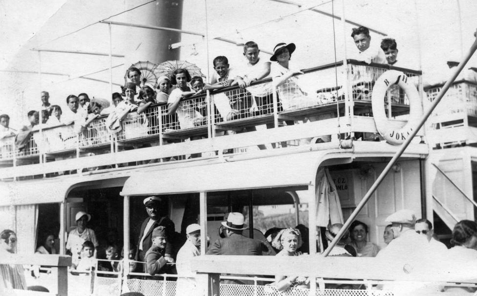 """A Helka és a Kelén mellett a Jókai csavargőzös volt a balatoni kirándulók harmadik kedvenc hajója. 1913-ban építette az Első Dunagőzhajózási Társaság óbudai gyáregysége, és azért nevezték el Jókai Mórról, mert a """"magyar Verne Gyula"""" imádott Balatonfüred és a déli part között ingázni a menetrend szerinti gőzhajójáratokkal. Sőt, Füreden írta meg az ifjúság rettegett féltéglányi kötelező olvasmányát, Az arany embert is, amihez a Krisztyán Tódor halálát okozó balatoni jégzajlásokat is testközelből figyelte meg. A fenti fotó 1932-ben készült: az utasok szemmel láthatóan legalább olyan jól érezték magukat a gőzhajón, mint Jókai."""