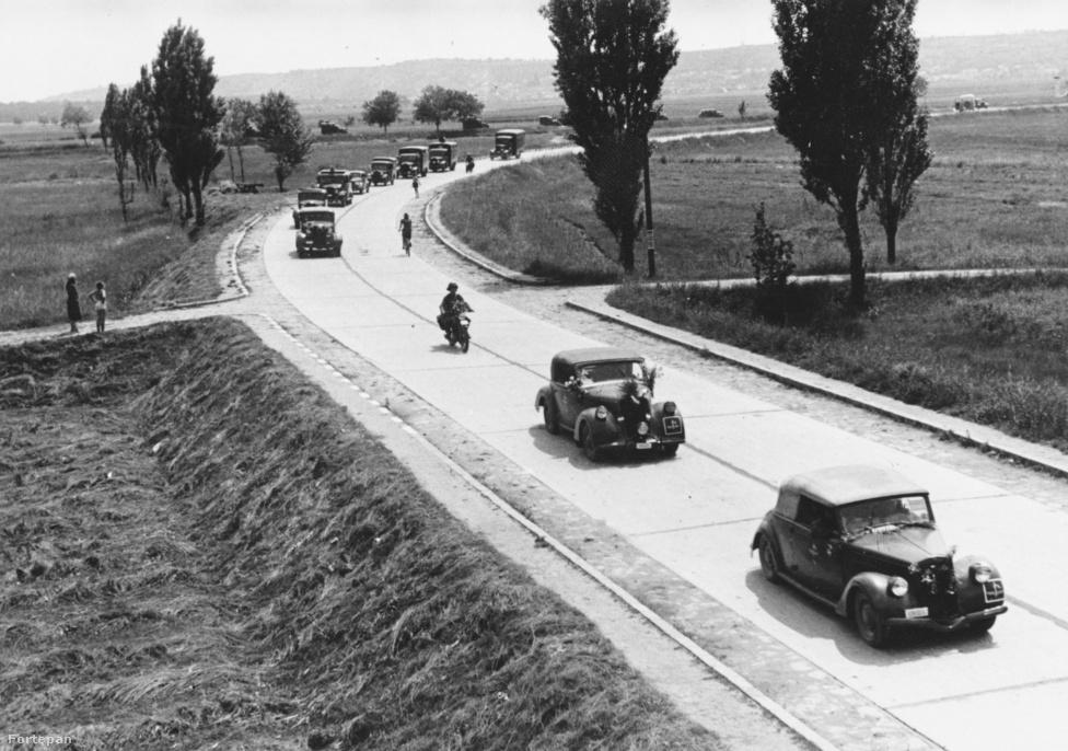 A fenti képen 1942-ben, Érd mellett koptatja a balatoni műutat a Magyar Királyi Haditudósító század menetoszlopa. Ha pár évvel korábban ugyanitt lefotózták volna ezt a ritkaságszámba menő kocsisort, a járművek nem az úttest jobb oldalán, hanem a balon haladtak volna - a jobboldali közlekedést ugyanis az 1941. június 26-án kiadott 187 000/1941-es BM rendelet rögzítette. Igaz, a hazai németbarát újságok már jóval korábban követelték változtatást, mivel Ausztriában 1938. szeptember 19-től, Csehszlovákiában pedig 1939 május 1-től tértek át a jobboldali közlekedésre, a korabeli média hangadói pedig az idegenforgalom visszaesésével riogatták az olvasókat, amennyiben nem változtatjuk meg a hajtási irányt.