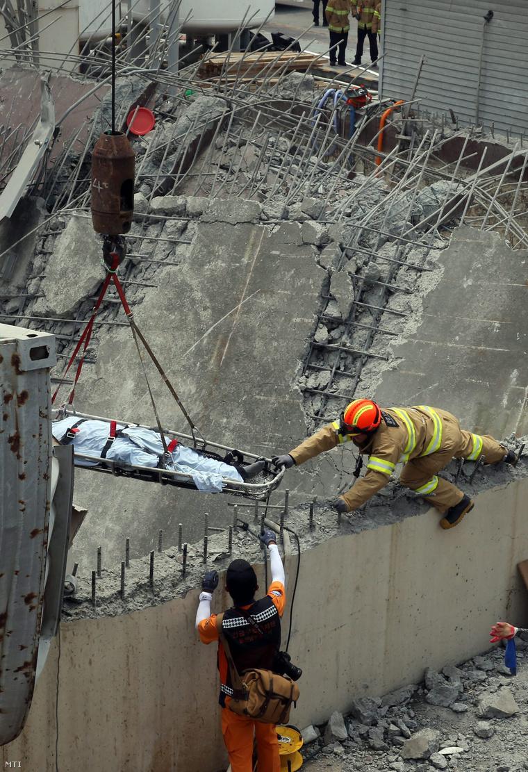 Egy áldozat holttestét emelik ki a romok alól a dél-koreai Ulszanban 2015. július 3-án, miután felrobbant egy mérgező hulladékkal megrakott tartály a Hanwha Chemical vállalat vegyi üzemében.
