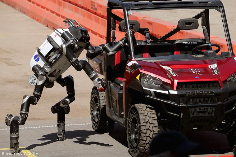 A Jet Propulsion Labs által fejlesztett RoboSimian mászik ki egy Polaris gépjárműből a DARPA robotoknak kiírt ügyességi versenyén