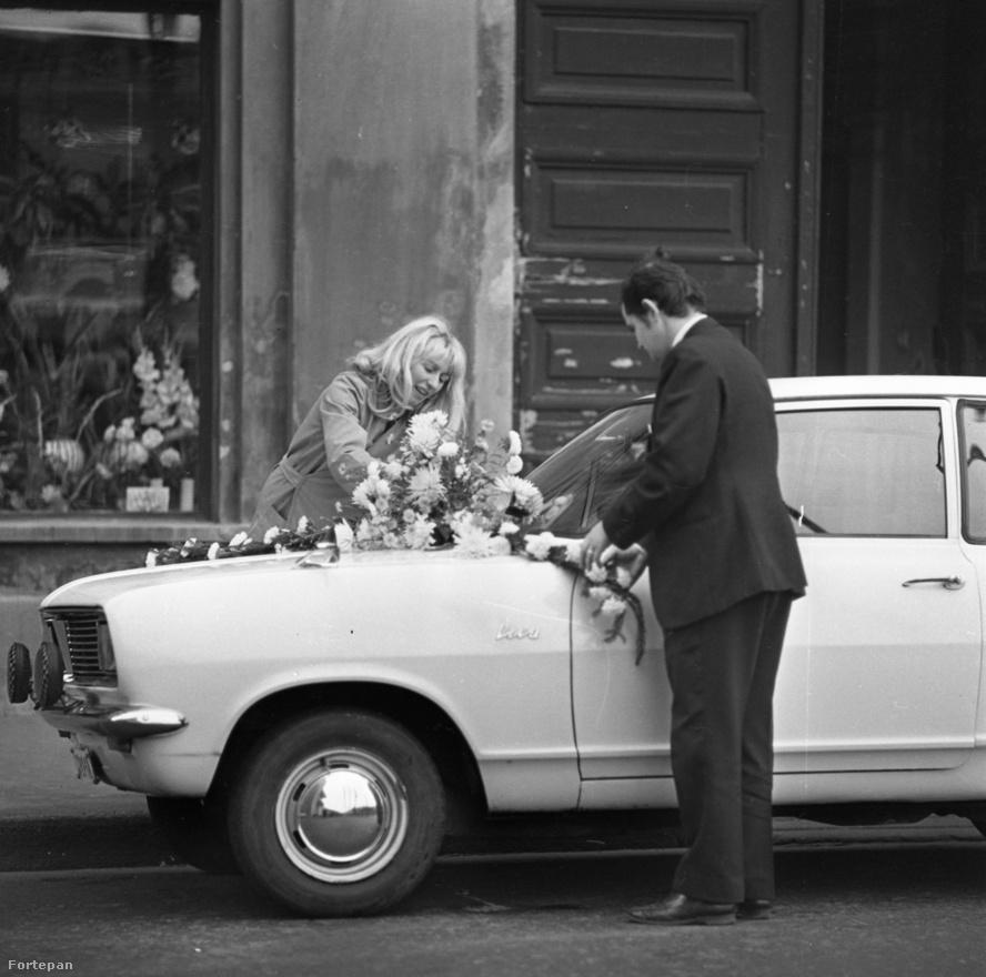 Ez a fiatal pár maga díszíti fel a nyugati kocsit, amit valószínűleg egy gazdag nagybácsitól vagy külföldi rokontól kaptak kölcsön. A templomi                          esküvő talán már megvolt, most jöhet az állami. Eddigre a rendszer szelídült annyit, hogy az ember nem vágta el feltétlenül a karrierjét, ha kiderült róla a templomi esküvő. Vélhetően a belvárosban, a nemrég átadott Inter-Continental szálló (Ma Marriott) csúf háta mögött vagyunk, az Apáczai csere János utcában. Az is lehet persze, hogy a vőlegény sikeres sportoló, vagy híres színész – akkoriban az utca embere tőlük (és csakis tőlük) nem irigyelte a nyugati kocsit.