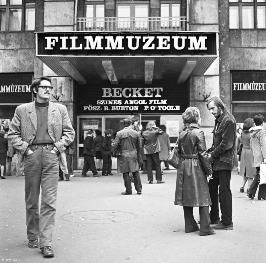 A Károly körút és Dohány utca sarkán, a mai Belvárosi Színház helyén működött évtizedeken át a hallatlanul népszerű Filmmúzeum nevű mozi, ahol sok filmet játszottak, igen kevésszer. Afféle szelep volt ez, minőségi programmal. Itt nem voltak kötelező szovjet, bolgár és NDK-beli filmek, csak a filmművészet java – egyáltalán nem csak régi filmek. Olyan népszerű volt, hogy mindig volt jegyüzér is. (A fiatalok kedvéért: olyan személy, aki előre felvásárolt jegyeket, és azt nagy felárral adta tovább.) Talán a háttal álló férfi? Akkoriban a legújabb filmek 1-2 évvel követték a világpremiert. Valakik abban is döntöttek, hogy ez és ez a film jöhet Magyarországra, de csak a Filmmúzeum programja keretében.