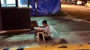 A McDonald's fényeinél írja a leckéjét egy manilai hajléktalan kisfiú