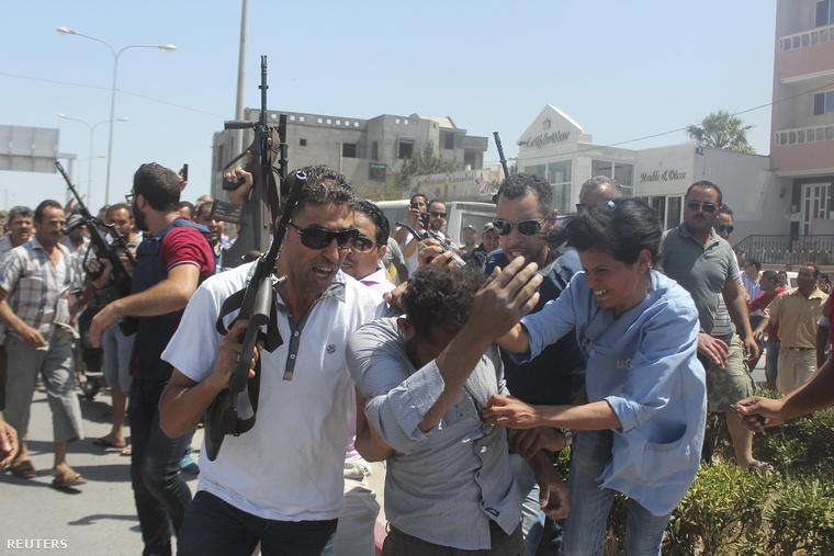 A tunéziai támadásban való részvétellel gyanúsított férfit vesznek körbe rendőrök és a feldühödött tömeg Szúszában
