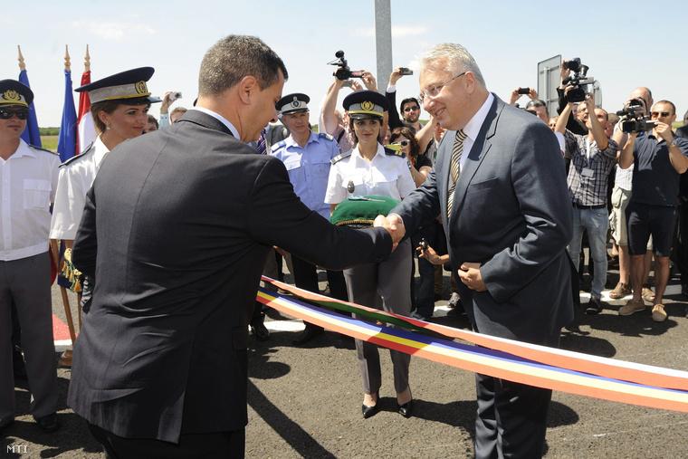 Semjén Zsolt miniszterelnök-helyettes (j) és Marius Nica a román kormány európai alapokért felelős minisztere kezet fog mielőtt átvágják a két ország nemzetiszínű szalagját.
