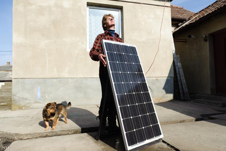 Tóth Ferenc Györgyné a napelemet igazítja háza udvarán Mátraverebélyen. Otthonában három éve kikapcsolták az elektromos áramot. Házában az áramellátást egy napelemből szobakerékpárra szerelt generátorból és akkumulátorból álló berendezés biztosítja amelyet egy sportegyesület adományaként az önkormányzattól kapott. (2012.)
