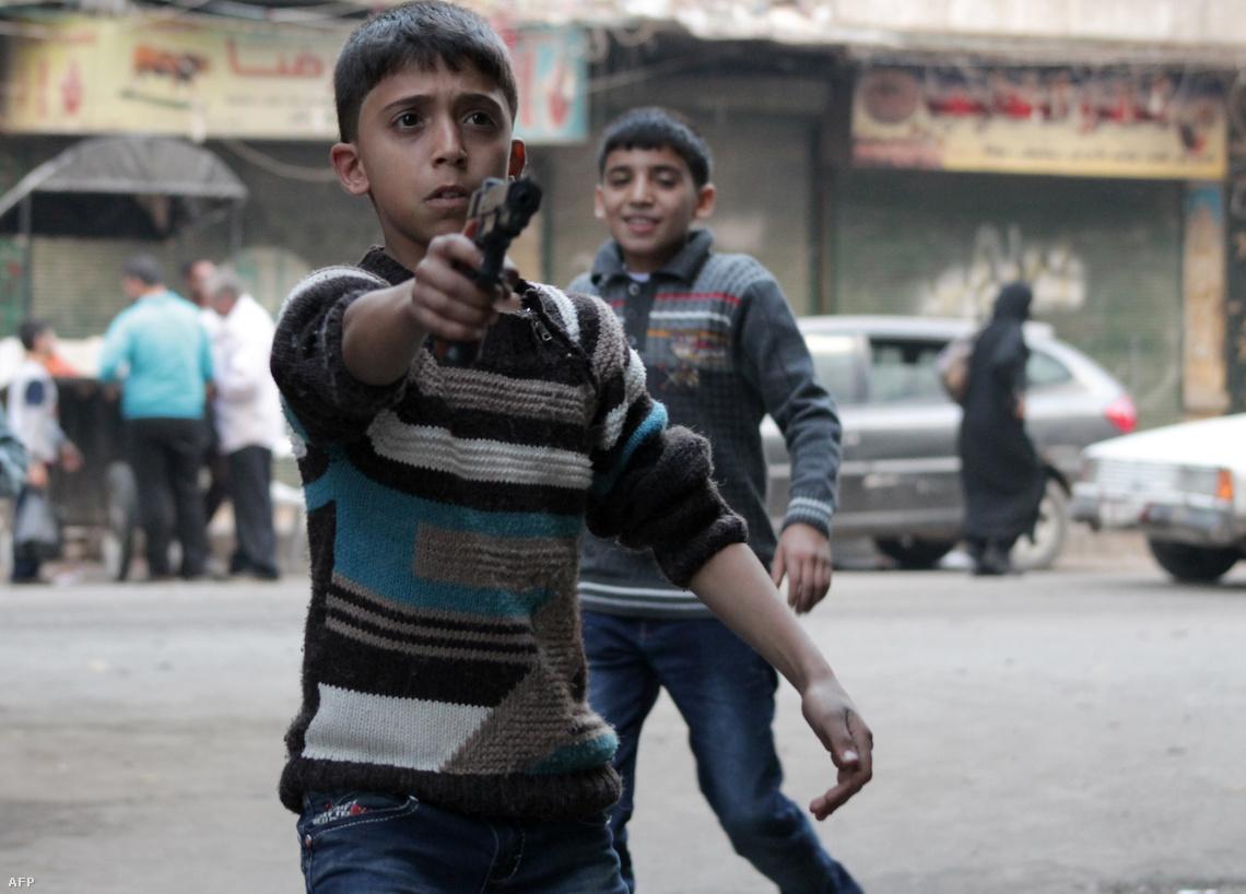 Játékfegyverrel játszik egy szíriai fiú a polgárháború dúlta Aleppóban.