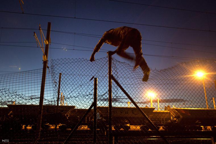 Átmászik egy bevándorló a Londont Párizzsal a La Manche csatorna alatt összekötő Csatorna-alagút közelében a franciaországi Calais-ban