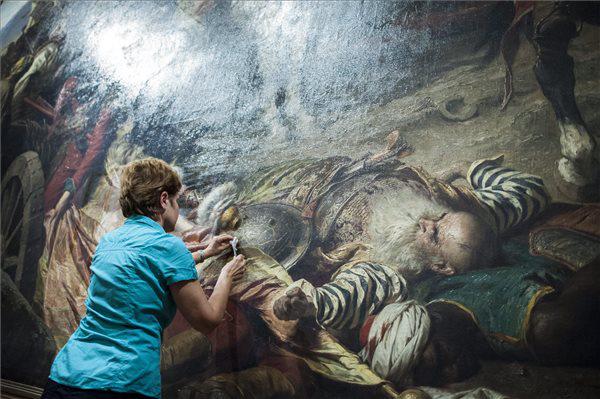 Festő-restaurátor tisztítja Benczúr Gyula Budavár visszavétele 1686-ban című festményét