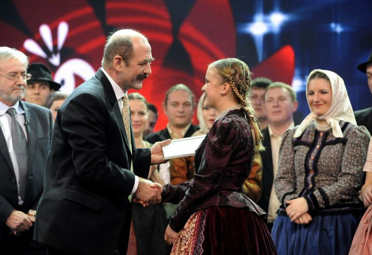 Kelemen László, a Hagyományok Háza főigazgatója átadja a díjat az énekes és szólisták kategória első helyezettjének, Csizmadia Annának MTI Fotó: Zih Zsolt