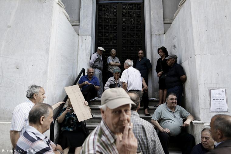 Görög nyugdíjasok várakoznak a Nemzeti Bank athéni épülete előtt.