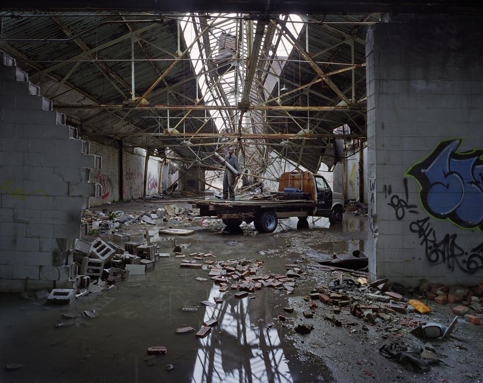 Fémhulladékot gyűjt egy férfi egy elhagyatott detroiti autógyár romos csarnokában.