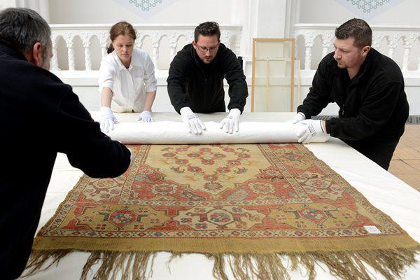 A Törökországban nyíló Oszmán-török szőnyegek az Iparművészeti Múzeum gyűjteményéből című kiállításra csomagolják el az egyik kiállítási tárgyat a múzeum dolgozói (Fotó: Kovács Tamás, MTI)