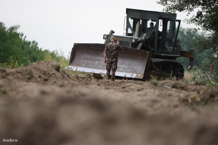 Egy honvédségi lánctalpas munkagép az ideiglenes műszaki határzár építésének előkészítéseként földmunkákat végez a magyar-szerb határon Mórahalom közelében.