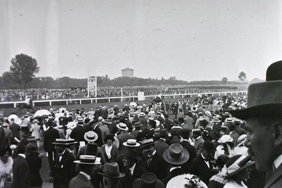 Hogy az Alexander Girardi, osztrák színészről elnevezett kalap mennyire népszerű volt a század első évtizedében, jól látszik ezen a képen. A szalmák mellett a szintén akkoriban elterjedő puhakalapokból is látni párat, s mutatóba néhány régi vágású keménykalapot is. A fénykép a régi lóversenytéren készült, nagyjából a mai Puskás Ferenc Stadion helyén. A létesítményt az első világháború végén zárták be. A háttérben az azóta szintén lebontott Stefánia úti víztorony látszik.