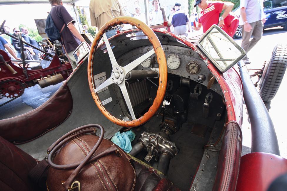 Belső kép az 1935-ös Alfa Romeo Tipo B versenykocsiból. Gyönyörű a patina, a kopottság, de ami a legcsodásabb: a differenciálmű lényegében a vezető kanóca alatt van. A fura konstrukció oka: a kétfelé osztott kardántengely miatt a vezetőülést lejjebb lehetett tenni, nagymértékben javítva ezzel a kocsi légellenállásán.