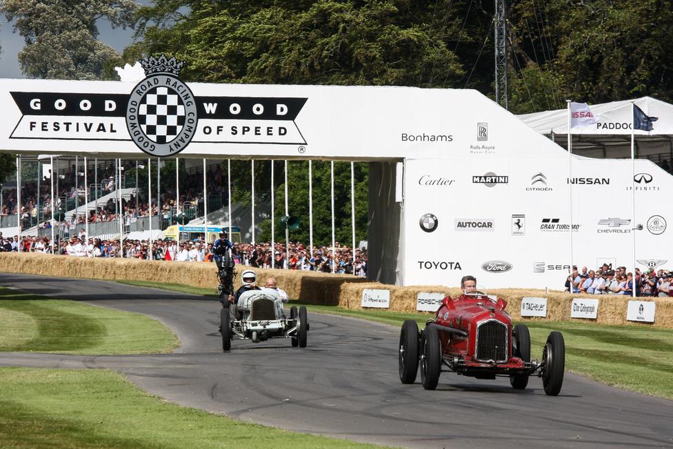Az Earl of March kastélya előtti széles részen járunk. Csilivili újdonság a vénség előtt: a háttérben a fehér autó egy Halford Special versenykocsi 1925-ből, amelyet James Halford mérnök, repülőgépmotor-tervező készített. Talán nem is az az igazán érdekes, hogy a Halford's ma Anglia legnagyobb autós alkatrészlánca (vö: Bárdi v. Unix-Trade), hanem hogy ezen a kocsin már 1925-ben turbófeltöltő volt. Hogy mi az a piros, amit üldöz? Egy Alfa Romeo Tipo B. Ez a versenyautó volt az 1932-33-as Grand Prix-szezon legsikeresebb típusa, bár a konkrét példány 1935-ös, Tazio Nuvolari ezzel tudott nyerni az akkor már rémesen sokkal erősebb Auto-Unionok és Mercedesek ellen. Padlógázon, szakadó esőben.