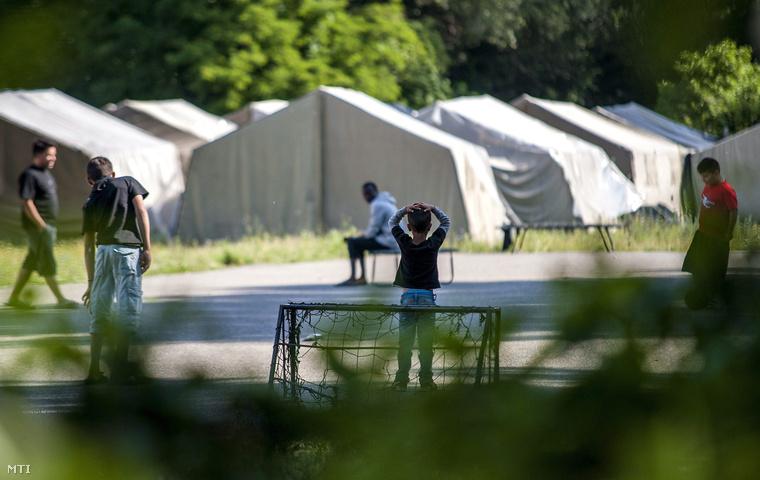 Gyerekek futballoznak a vámosszabadi menekülttábor udvarán felállított sátrak mellett 2015. június 30-án.