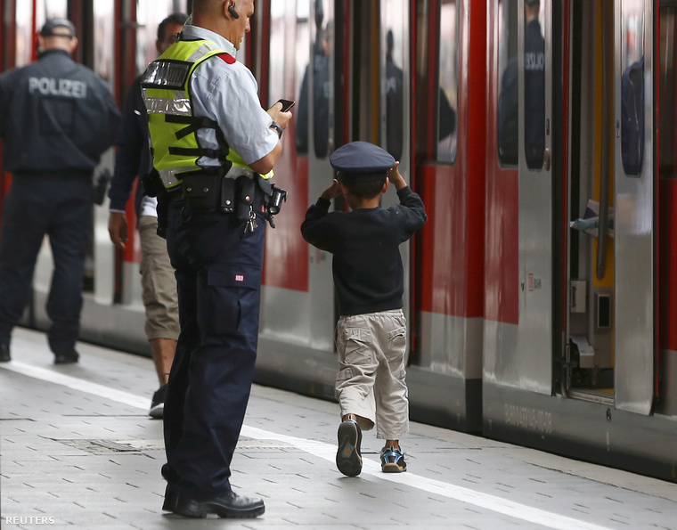 Német rendőr kalapjával játszik egy fiú, aki most érkezett Münchenbe.
