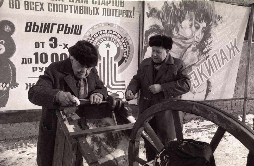 A plakátokon Misa mackó, a moszkvai olimpia kabalafigurája, mellette az Ekipázs (Legénység) című nagy szovjet repülős katasztrófafilm, melynek abban az évben 70 millió nézője volt. Elől, alul, velünk egy beregszászi idős vándorköszörűs.