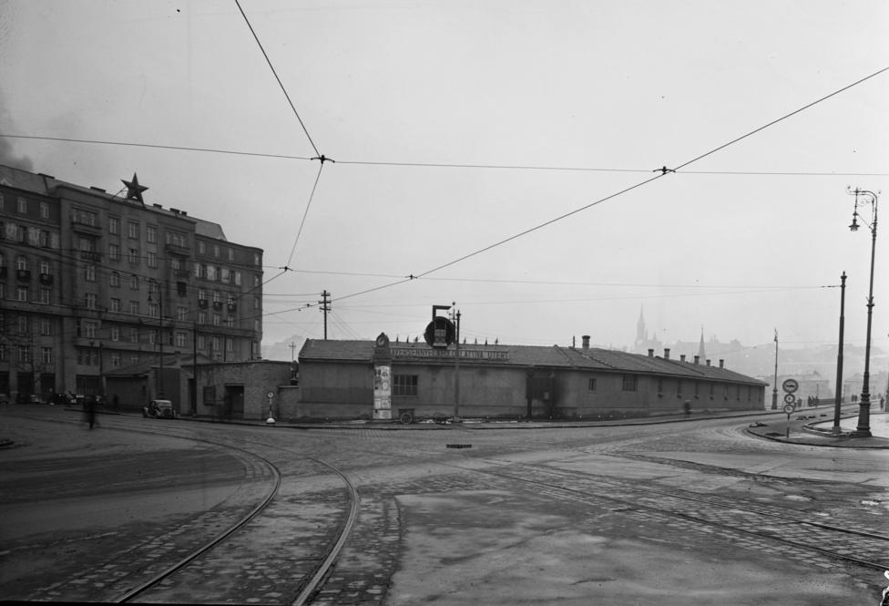 Barakkok mögött folyik a munka a Kossuth téren. Jobbra a háború után ideiglenesen felállított Kossuth hídra kanyarodhatunk, balra a Miniszterelnöki Hivatal látható. Ez utóbbi úgy néz ki, mint valami szocreál remekmű, tetején a vörös csillaggal, de valójában a néhány éve megszépült Wellisch-palota az, akkor még kupola nélkül.
