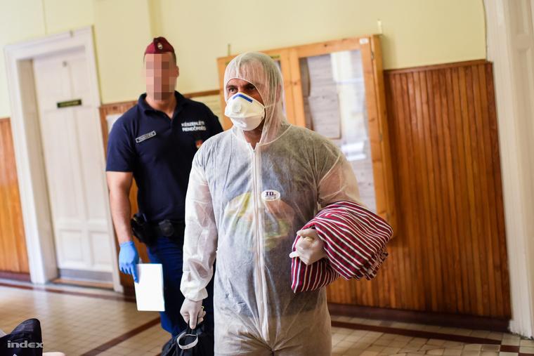 A képen látható férfit bőrbetegség miatt öltöztették védőruhába. A menekültek az utcai ruhájukban állhattak bíróság elé.