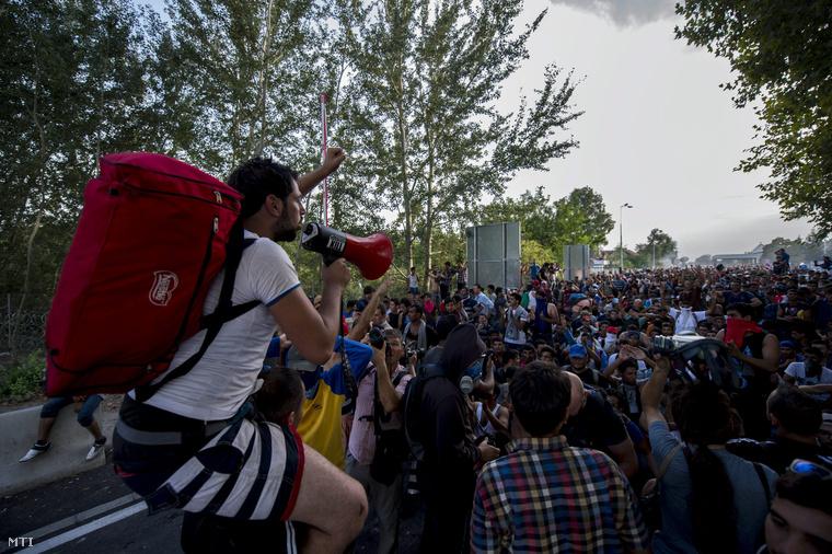 Egy migráns beszél hangosbeszélőn társa nyakában a Horgos-Röszke határátkelőhely magyar oldalán 2015. szeptember 16-án.