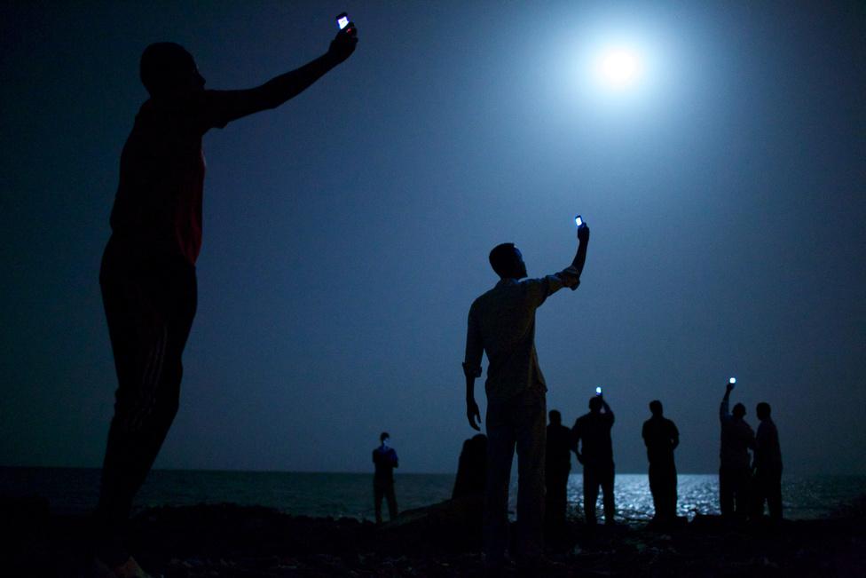 """2014. Afrikai kivándorlók Dzsibuti városában az olcsó szomáliai mobiltelefonos hálózat segítségével próbálnak minimális kapcsolatot teremteni a családtagokkal.A szomszédos Szomáliából, Etiópiából és Eritreából Európába és a Közel-Keletre induló menekültek gyakran tartanak pihenőt Dzsibutiban. Önöknek is feltűnhet, hogy a 2014-es győztes merőben más, mint a korábbi díjnyertes fotók. Szakítva 60 éve gyakorlatával, a zsűri 2014-ben olyan képet választott győztesnek, ami a sokkoló látvány helyett inkább elgondolkodtat.""""A munkák díjazásakor az esztétikai és az újságírói teljesítmény egyformán meghatározó volt"""", fejtette ki Gary Knight, a zsűri elnöke. A rendhagyó kiemelés nem csak visszaszólt a korábbi évek szinte egymásra licitálóan véres jeleneteire, de a jövőbe is mutatott: a mobiltelefonnal navigáló menekültek képe az idei év legfontosabb világpolitikai eseményét vetítette előre."""