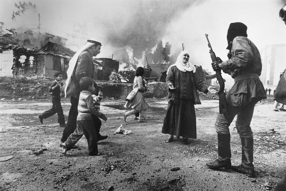 1977. Bejrút, Libanon. Palesztin nő könyörög egy falangista fegyveresnek a kelet-bejrúti Karantina városrészben.Aznap reggel a falangisták megtámadták és elűzték a városrész zömmel palesztin menekült lakóit, otthonukat felgyújtották, több száz embert megöltek. A karantinai mészárlás volt az egyik első erőszakos esemény a libanoni polgárháború kezdetén. A francia Françoise Demulder, az esemény szemtanúja az első női fotográfus volt, aki elnyerte Az év fotója díjat a könyörgő palesztin asszony megrendítő fotójával.